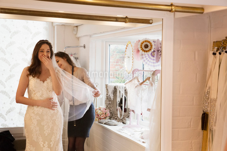 A bride, a young woman trying on a wedding dress with lace overlay and veil, her hand to her face inの写真素材 [FYI02258530]