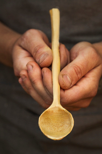A man's hands holding a handcrafted hand made wooden spoon with a long slender handle and round poliの写真素材 [FYI02258533]