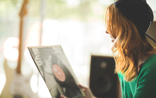 A woman looking at a record sleeve.の写真素材 [FYI02258539]