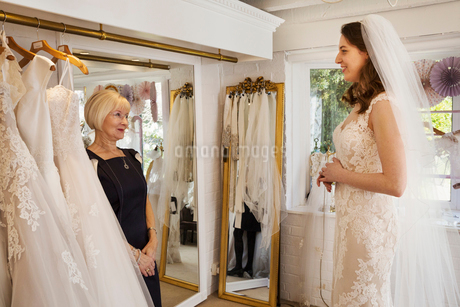 A woman, a bride to be, trying on dresses with the help of a sales assistant, in a wedding dress shoの写真素材 [FYI02258549]