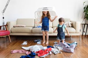 Young boy and girl with laundry basket over her head standing in front of sofa, laundry scattered onの写真素材 [FYI02258555]