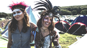 Two smiling young women at a summer music festival face painted, wearing feather headdress, standingの写真素材 [FYI02258562]