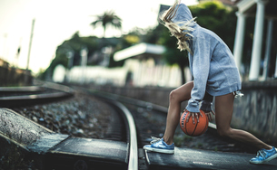 Young woman running across railway tracks bouncing a basketball.の写真素材 [FYI02258574]