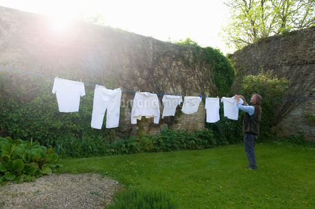 Man standing on a lawn in a garden, hanging up laundry on washing line.の写真素材 [FYI02258575]