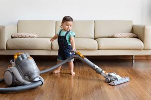 Young boy wearing denim dungarees, standing in front of sofa, hoovering hardwood floor.の写真素材 [FYI02258580]
