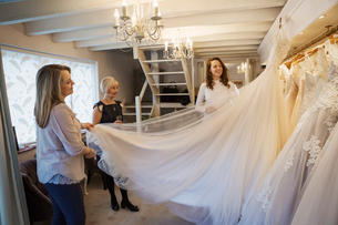 Three women in a wedding dress shop, one holding out the full skirt of a bridal gown.の写真素材 [FYI02258598]