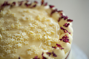 Close up high angle view of cake decorated with cream and purple flower petals.の写真素材 [FYI02258605]