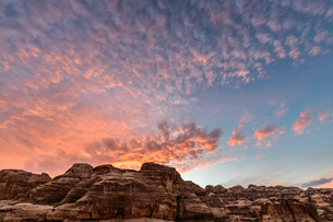 Rock formations in the Wadi Rum desert wilderness in southern Jordan at sunset, and the sun's rays rの写真素材 [FYI02258627]