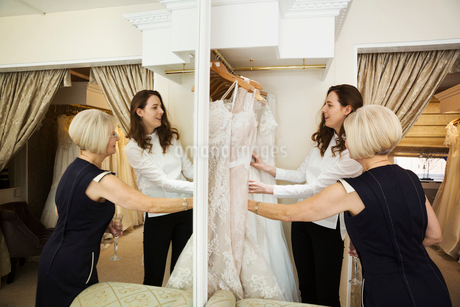 Two women, a client and retail advisor in a wedding dress shop, looking through the choice of gowns.の写真素材 [FYI02258634]