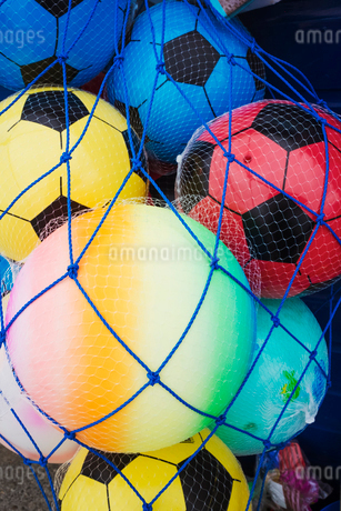 Close up of colourful plastic balls in a blue net.の写真素材 [FYI02258636]
