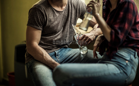 A man and a woman sitting and drinking from glass bottles on stools at a bar.の写真素材 [FYI02258637]