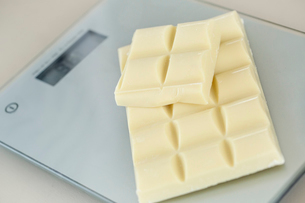 Close up high angle view of white chocolate on a digital kitchen scale.の写真素材 [FYI02258651]