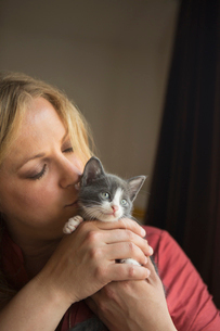 Woman holding a small grey and white kitten in her two hands, nuzzling it.の写真素材 [FYI02258659]