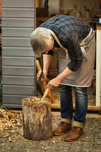 Craftsman woodcarver bending down and holding a hand axe, cutting a small piece of wood on a splittiの写真素材 [FYI02258667]