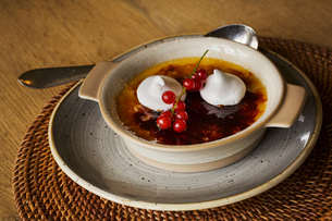 Close up of a dish of Creme Brulee with meringue and fresh red currants.の写真素材 [FYI02258672]