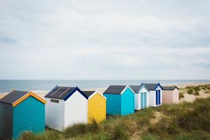 Row of colourful painted beach huts on a sandy beach under a cloudy sky.の写真素材 [FYI02258686]