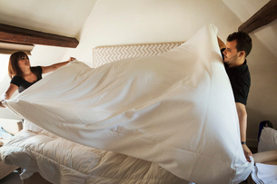 Man and woman standing in hotel room, making bed.の写真素材 [FYI02258695]