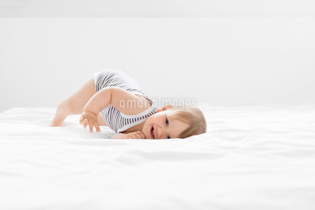 Baby boy wearing striped onesie lying on bed with white duvet.の写真素材 [FYI02258708]