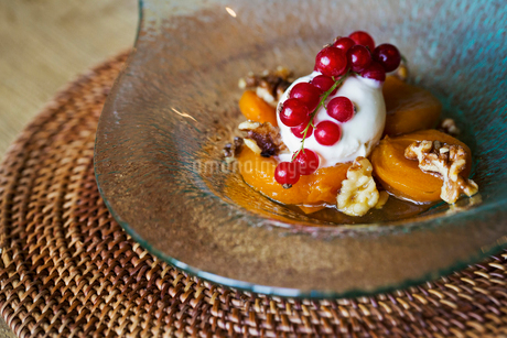 Close up of a dish of poached peaches with cream, walnuts and fresh red currants.の写真素材 [FYI02258725]