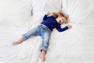 High angle view of girl with blond hair wearing jeans and blue top lying on her back on a bed.の写真素材 [FYI02258729]