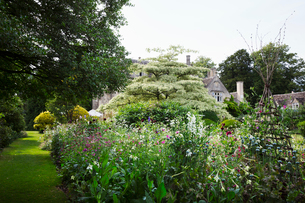 Exterior view of a 17th century country house from a garden with flower beds, shrubs and trees.の写真素材 [FYI02258745]
