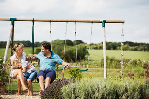 Man, woman and boy sitting side by side on a swing in a garden.の写真素材 [FYI02258747]