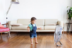 Young boy wearing denim dungarees, standing on hardwood floor in front of electric fan.の写真素材 [FYI02258761]