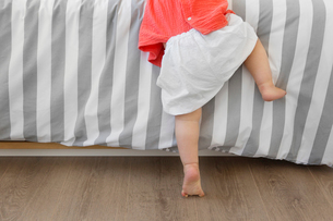 Rear view low section of barefoot baby girl trying to climb onto a bed with stripy duvet.の写真素材 [FYI02258767]