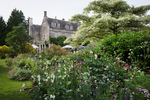 Exterior view of a 17th century country house from a garden with flower beds, shrubs and trees.の写真素材 [FYI02258770]