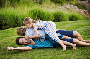 A man lying on the grass with his two children lying on top of him, playing.の写真素材 [FYI02258774]