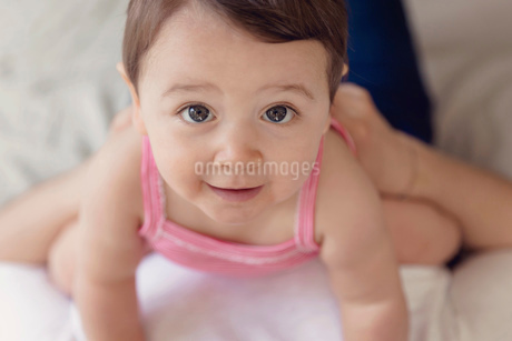High angle view of baby girl with brown hair wearing pink onesie, looking at camera.の写真素材 [FYI02258789]