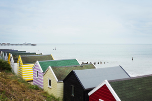 Row of colourful huts on a sandy beach under a cloudy sky.の写真素材 [FYI02258796]