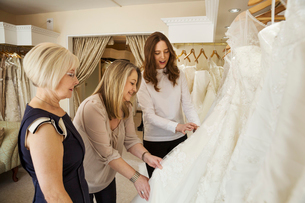 Three women, a client and two retail advisors in a wedding dress shop, looking through the choice ofの写真素材 [FYI02258811]