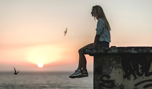 Side view of a young woman sitting on a wall with a sunset behind.の写真素材 [FYI02258817]