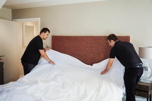 Two men standing in hotel room, making bed.の写真素材 [FYI02258830]