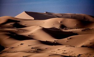 Sand dunes in wave shapes, formed by the action of wind and weather, in the desert.の写真素材 [FYI02258838]