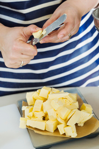 Close up of person wearing a blue and white stripy apron holding a knife, cutting butter into smallの写真素材 [FYI02258841]