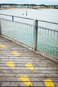 Yellow footprints on a traditional wooden pier in a coastal town.の写真素材 [FYI02258852]