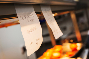 Close up of handwritten order tabs in a restaurant kitchen.の写真素材 [FYI02258854]