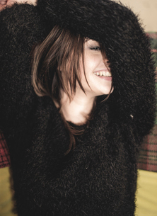 Portrait of smiling young woman wearing fluffy black jumper, arms raised over head.の写真素材 [FYI02258870]