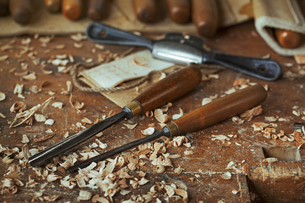 Close up of wood carving hand tools, chisels and wood shavings on a bench in a carver's workshop.の写真素材 [FYI02258879]