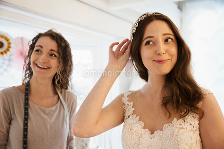 A young woman trying on hair accessories, and veil with a white lace overlay wedding dress, assistedの写真素材 [FYI02258891]