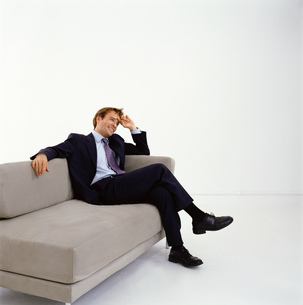 Businessman wearing dark suit sitting indoors on a sofa, hand on head, smiling.の写真素材 [FYI02258901]