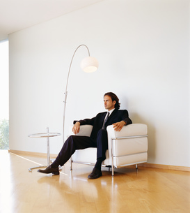 Businessman wearing dark suit sitting indoors on a leather armchair.の写真素材 [FYI02258910]