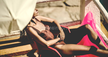 A young woman wearing a swimsuit reclining under a sun umbrella.の写真素材 [FYI02258919]