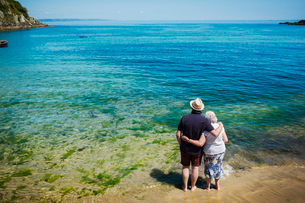 Rear view of elderly couple standing with arms around each other looking out over the vivid blue andの写真素材 [FYI02258953]
