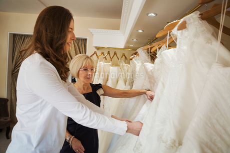 Two women, a young bride to be and a mature sales assistant looking through rails of wedding dressesの写真素材 [FYI02258963]