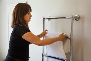 Woman standing in a bathroom, hanging fresh towel over metal towel holder.の写真素材 [FYI02258978]
