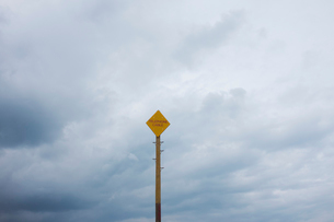 Yellow warning sign on pole against cloudy sky.の写真素材 [FYI02258983]