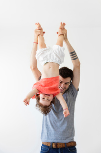 Man wearing grey T-shirt playing with baby girl in red top, holding her upside down by her feet.の写真素材 [FYI02258991]
